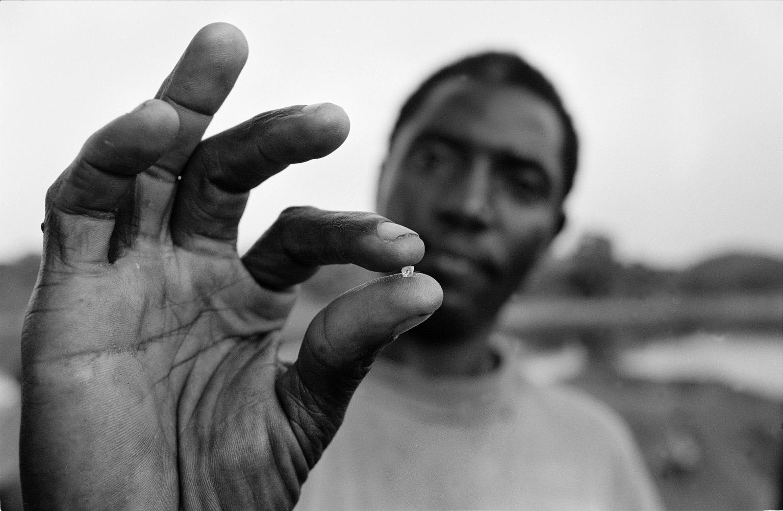 foto van de hand van een man die een kleine diamant vasthoudt en op de achtergrond is vaag zijn gezicht in het landschap erachter te zien