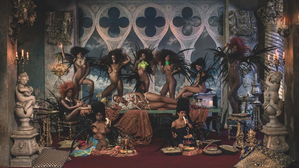 foto van Marc Lagrange van tien bijna naakte zwarte vrouwen tussen sculpturen en allerlei symbolische elementen