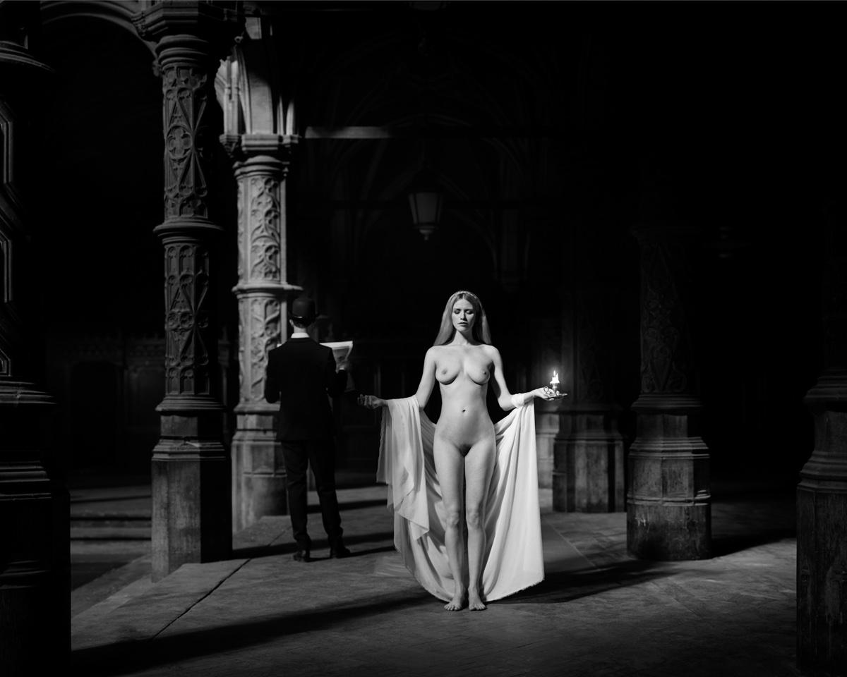 foto van naakte vrouw in kerk met wit doek en pilaren en achter haar een man in zwart pak met een groot boek