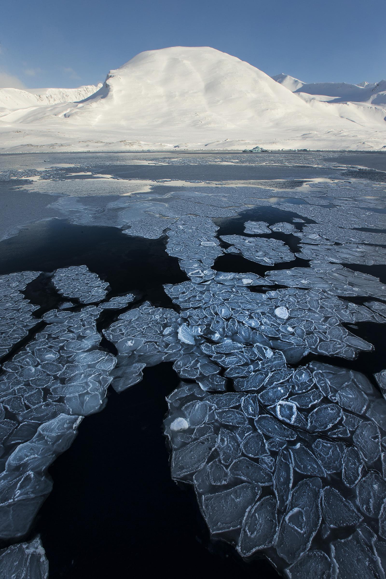 foto van water met gesmolten ijs bij Noordpool en in horizon een witte berg