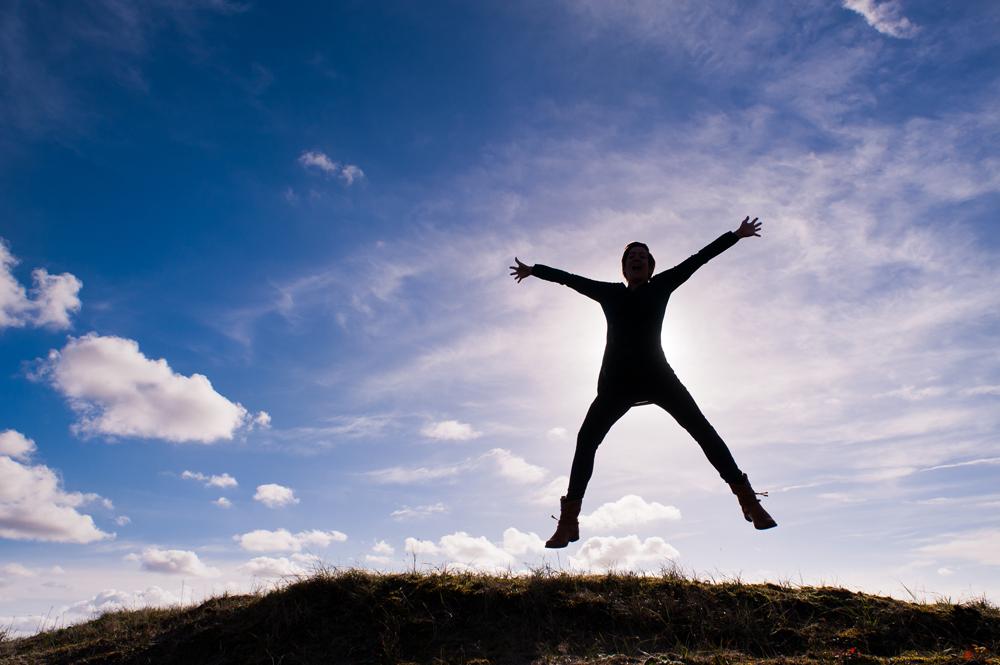 foto van een mens in silhouet met gespreide armen die springt op een heuvel en wolkenlucht erachter