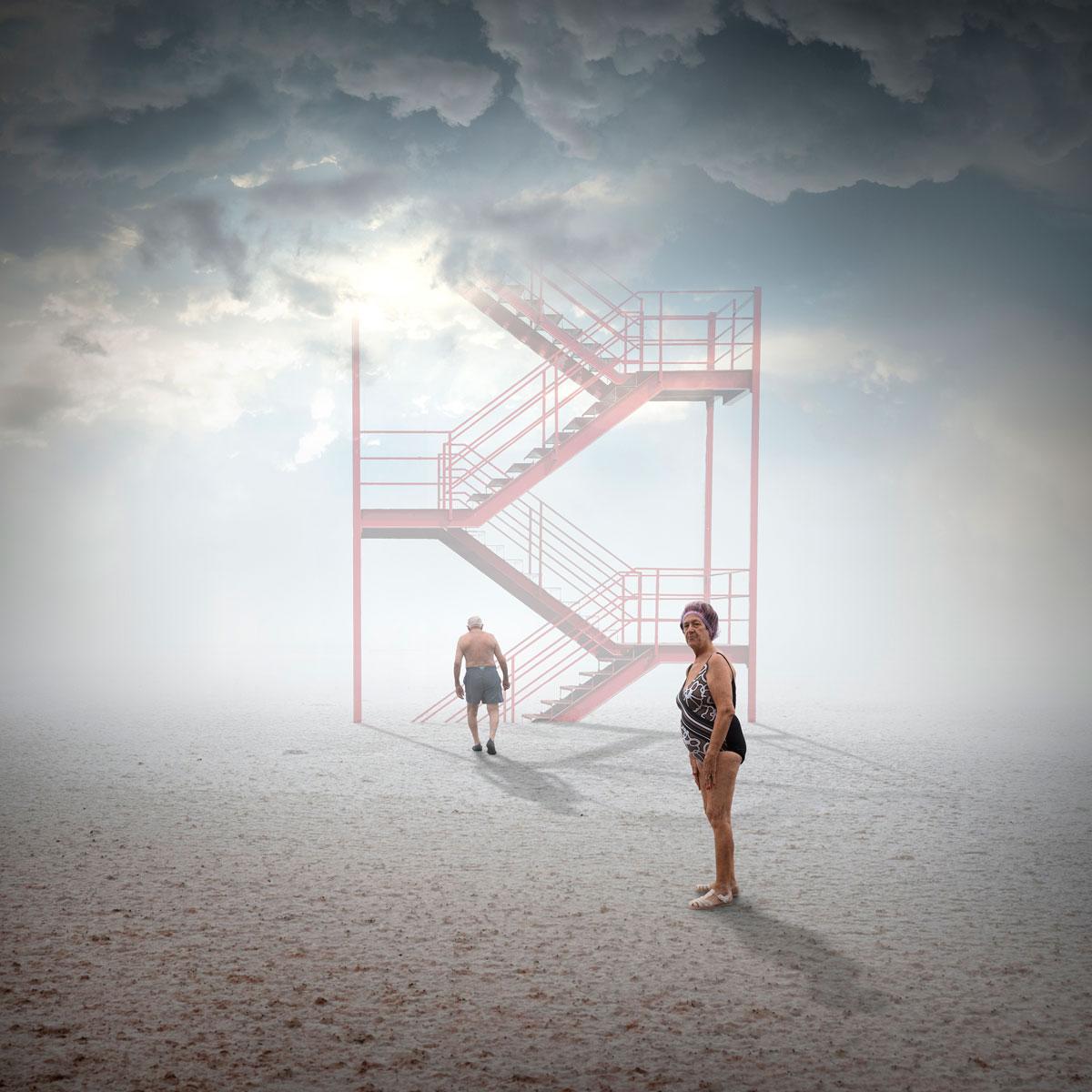 foto van oudere man en vrouw in badkleding op een zandvlakte bij futurische tyrap naar de hemel