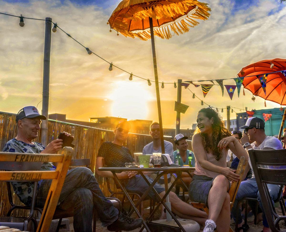 vrolijke foto van mensen op het terras van een strandtent met zon erachter die bijna ondergaat