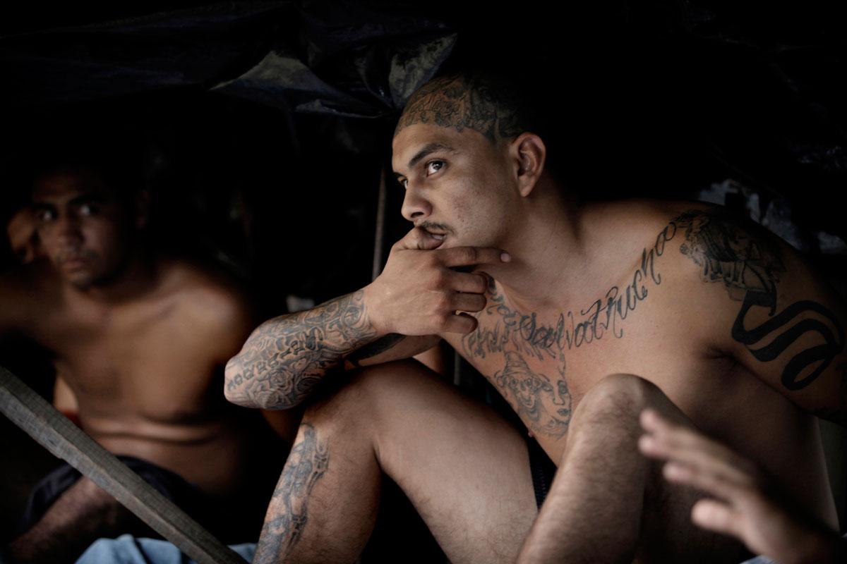 foto van twee donkere mannen ontbloot bovenlijf en benen zittend met veel tattoo's
