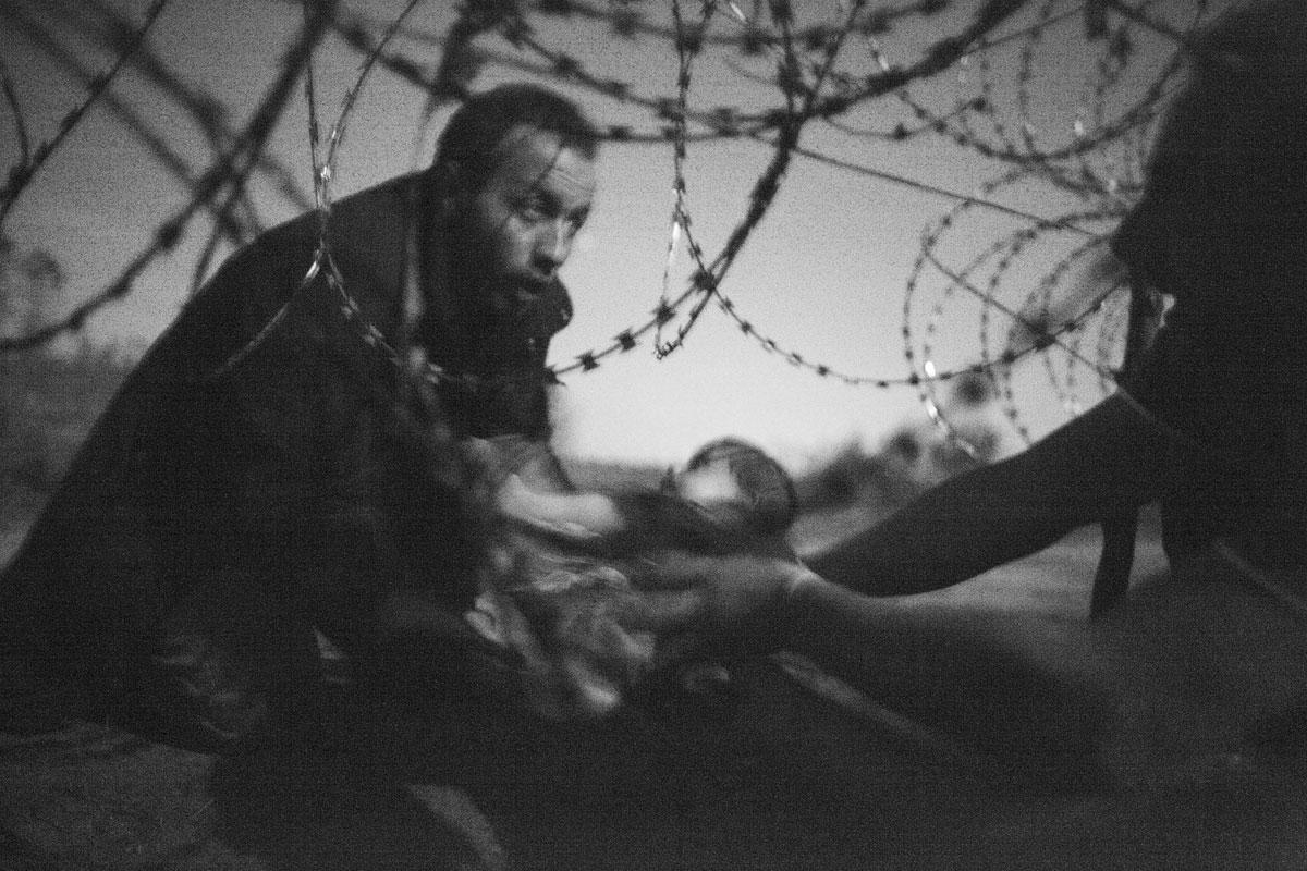 foto toont een man die een baby doorgeeft aan het hek bij de grens van Servië en Hongarije in Röszke.