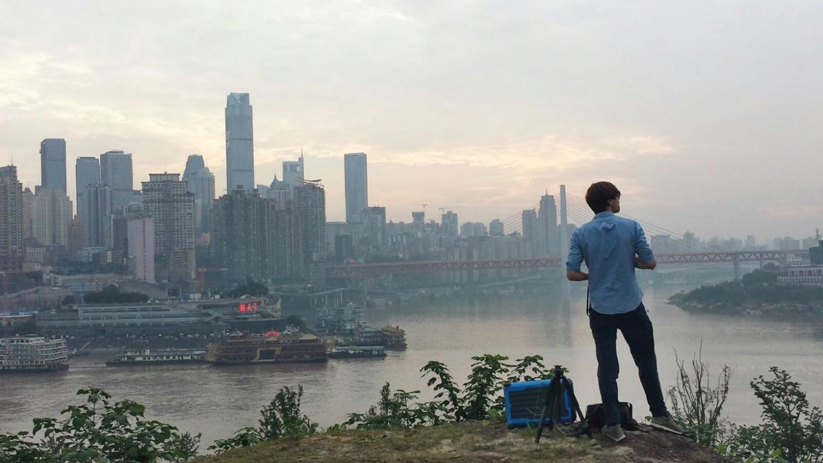 foto van een man die langs de oever van de Yangtze staat te kijken naar de stad