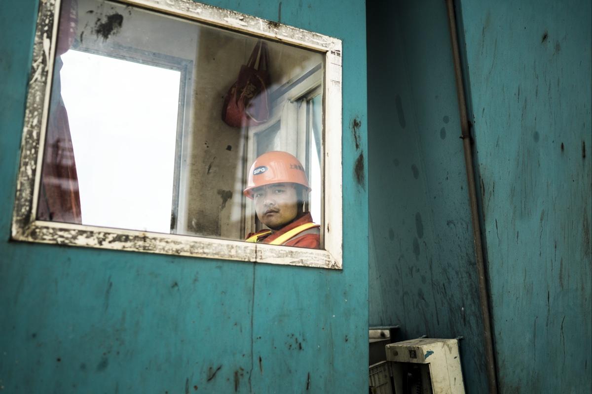 foto van Chinese werkman met helm achter raam in bouwkeet