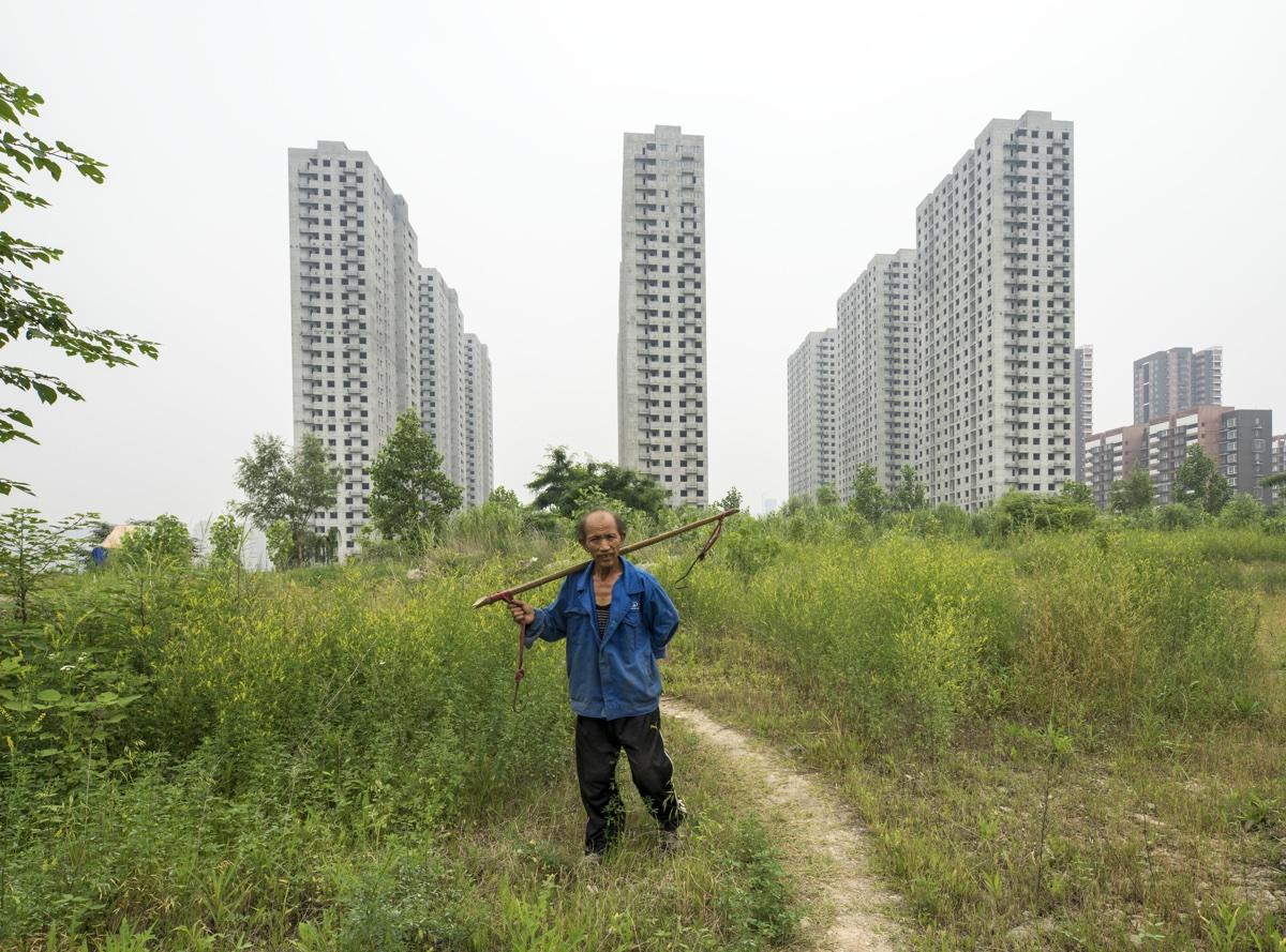 foto van flats van Shanghai met man met stok en touw op zijn rug ervoor
