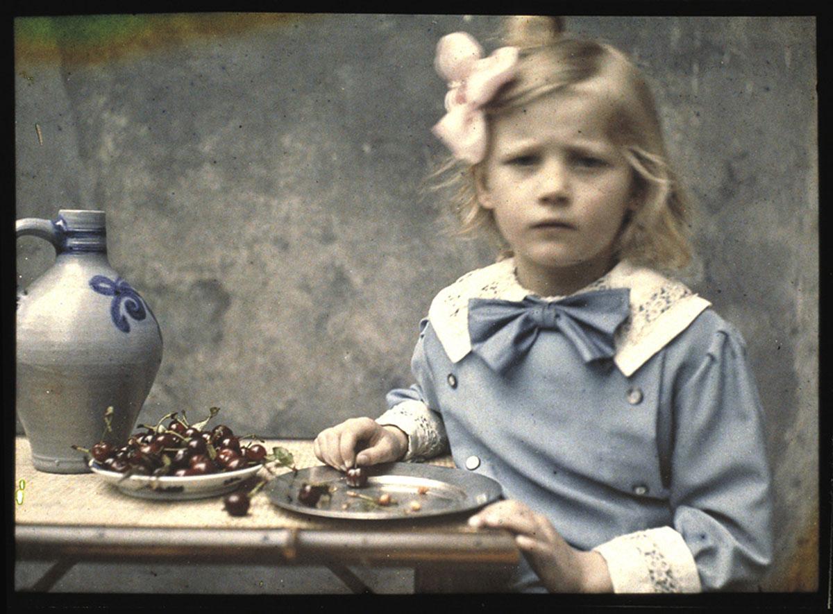foto van Marietje Zeegers, dochter van de fotograaf van rond 1900, waar ze aan een tafel met kersen zit