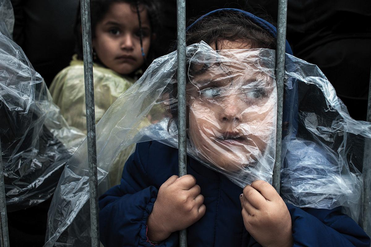 kind achter tralies die ze vasthoudt en hoofd er tegen aan drukt