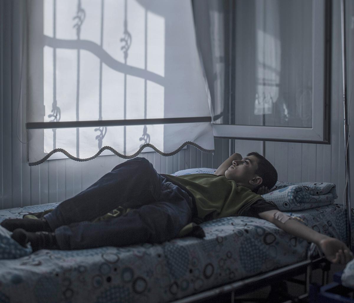 foto van jongen die op bed ligt en naar raam kijkt