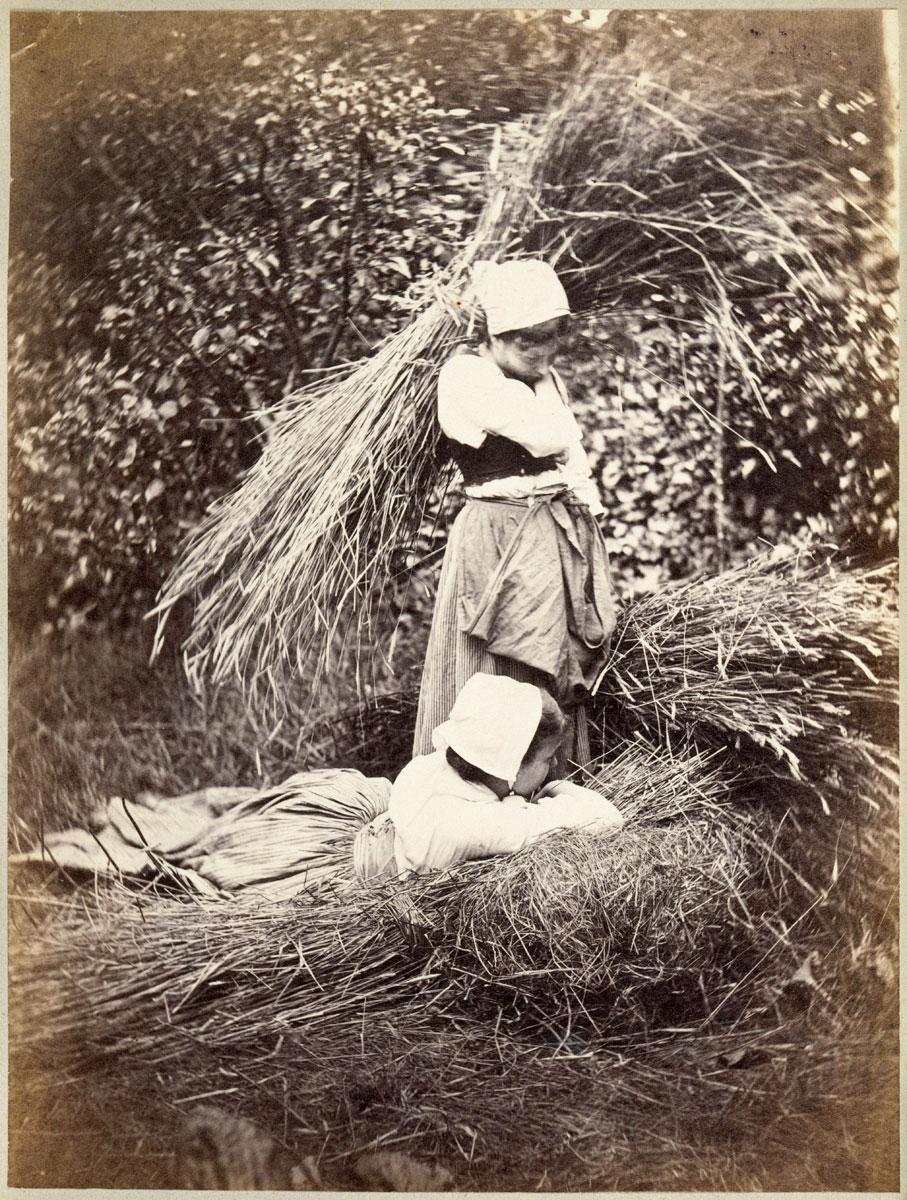 foto van twee boerinnen die hooi bijeenbinden in 1878