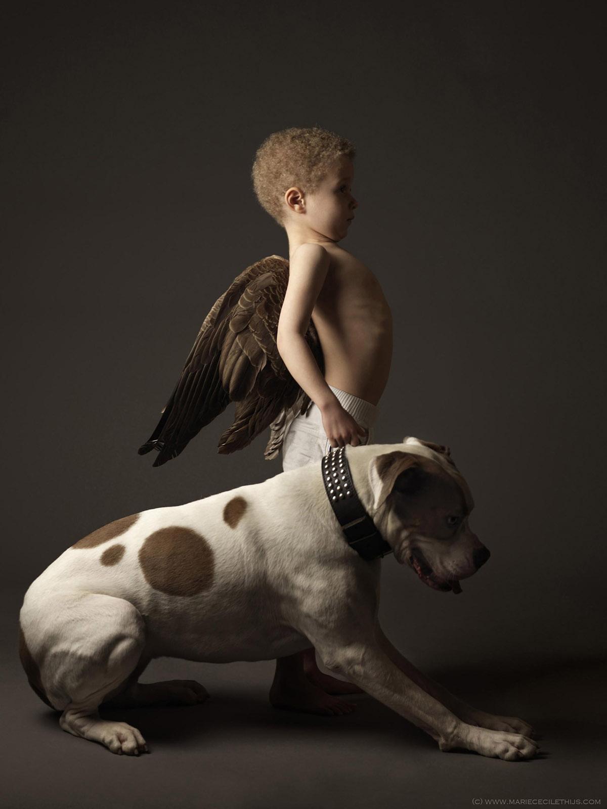 foto van Marie Cécile Thijs van jongen met vleugels op zijn rug en een hond naast zich