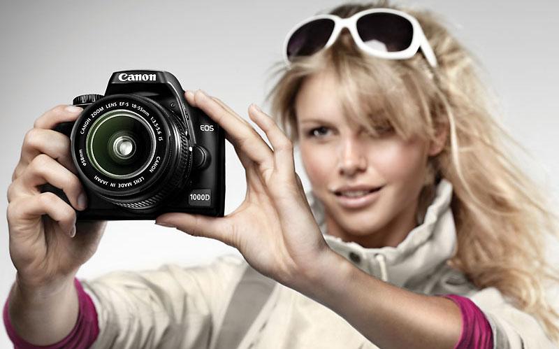 foto van een dame met zonnebril die een Canon camera vasthoudt