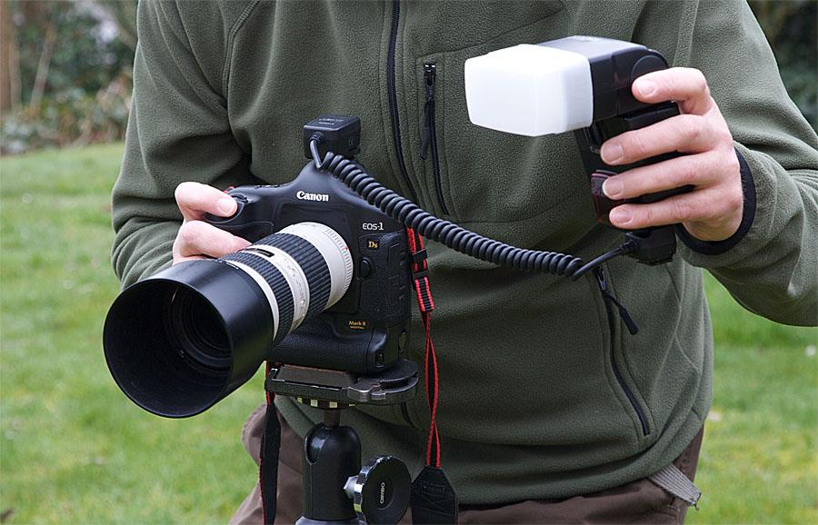 foto van camera met flitser via kabel vastgehouden door man