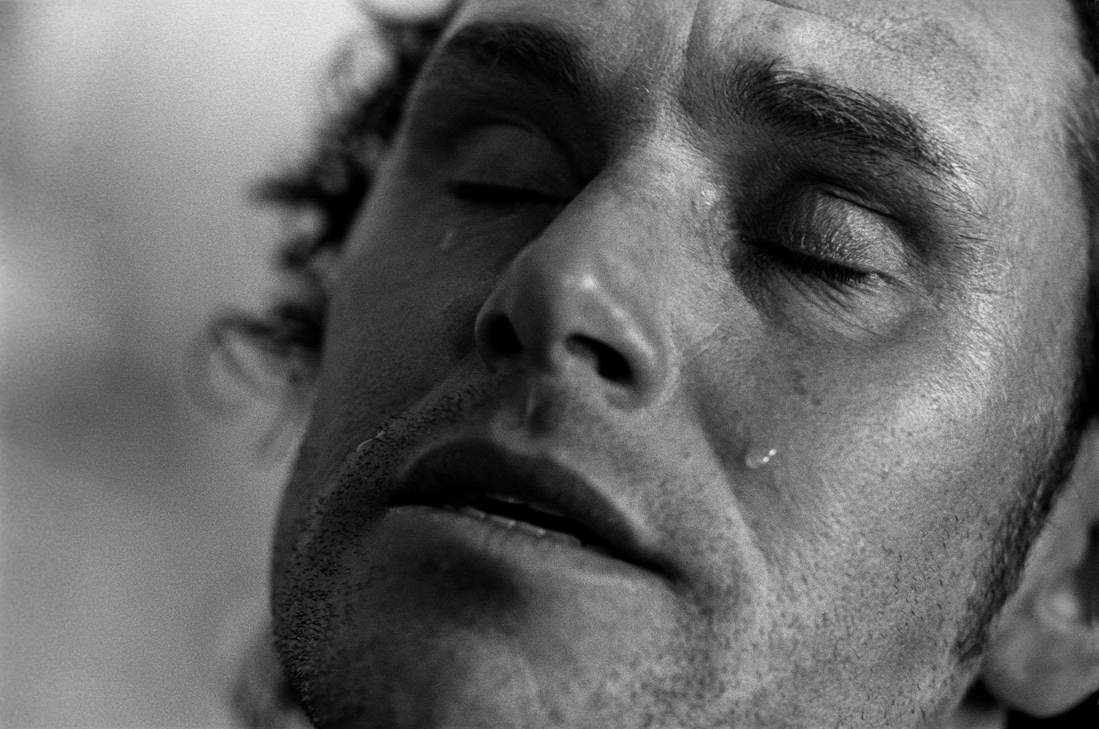 gezicht van man dichtbij met ogen dicht en traan over zijn wang