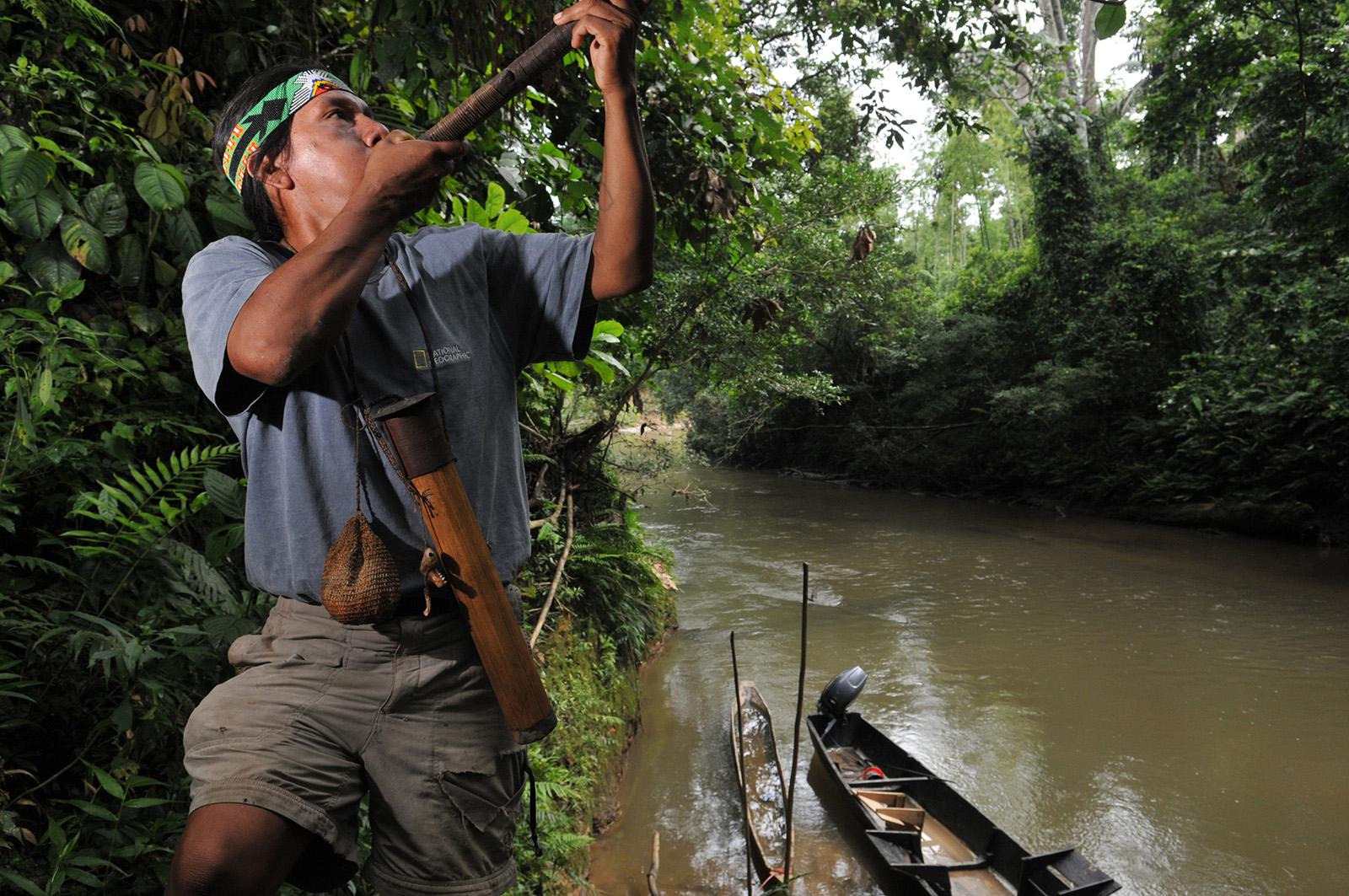 foto van een indiaan die bij een rivier met een boot in een bos blaast op een pijp die hij naar boven richt