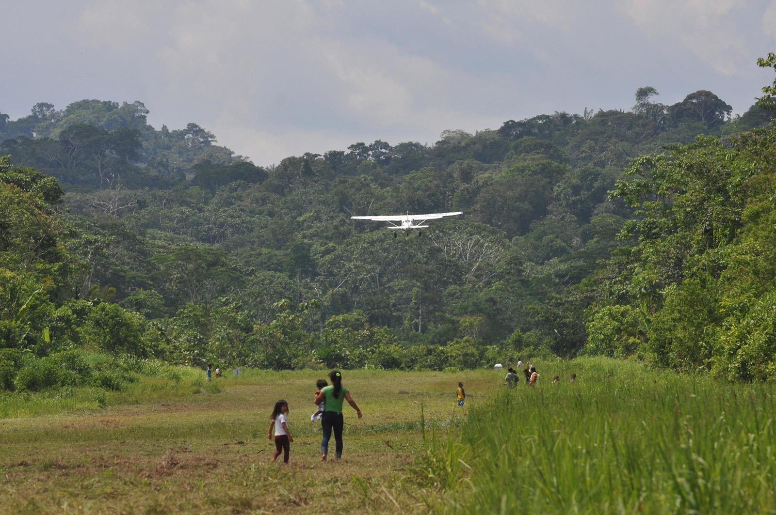 foto van mensen op een weide in Ecuador en een zweefvliegtuigje erboven zwevend