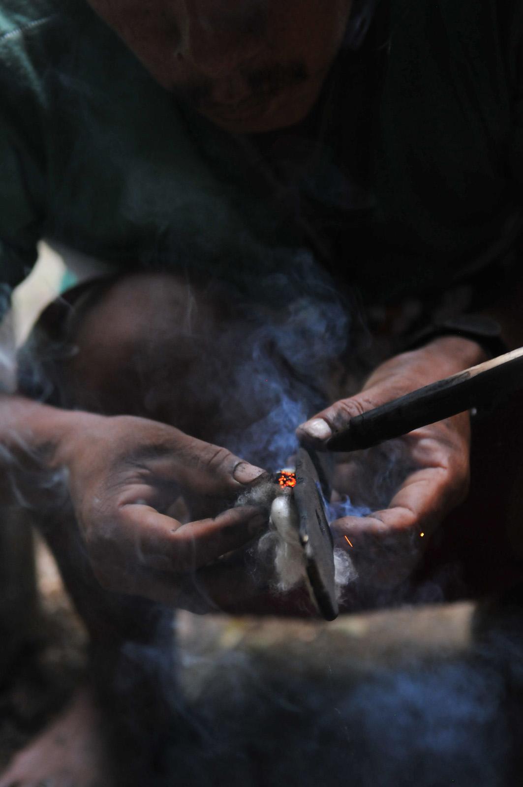 close up foto van handen van een indiaan die vuur probeert te maken met twee stokjes