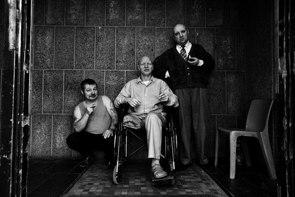 foto van drie mannen in een gevangeniscel, eentje knielend met sigaret, een in rolstoel met een been geamputeerd en eentje staat met stropdas en een pijp