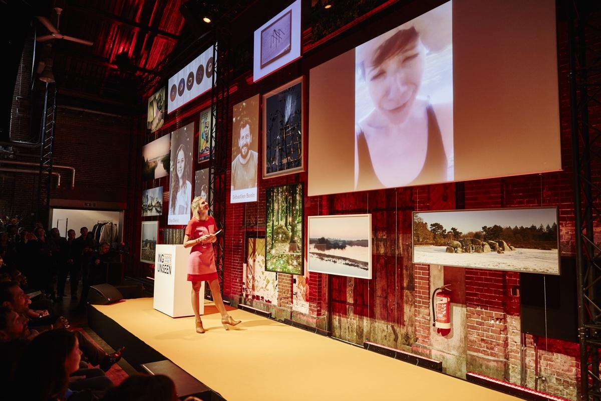 foto van presentatie door vrouw in rode jurk met foto's op groot scherm van Unseen talent award 2015