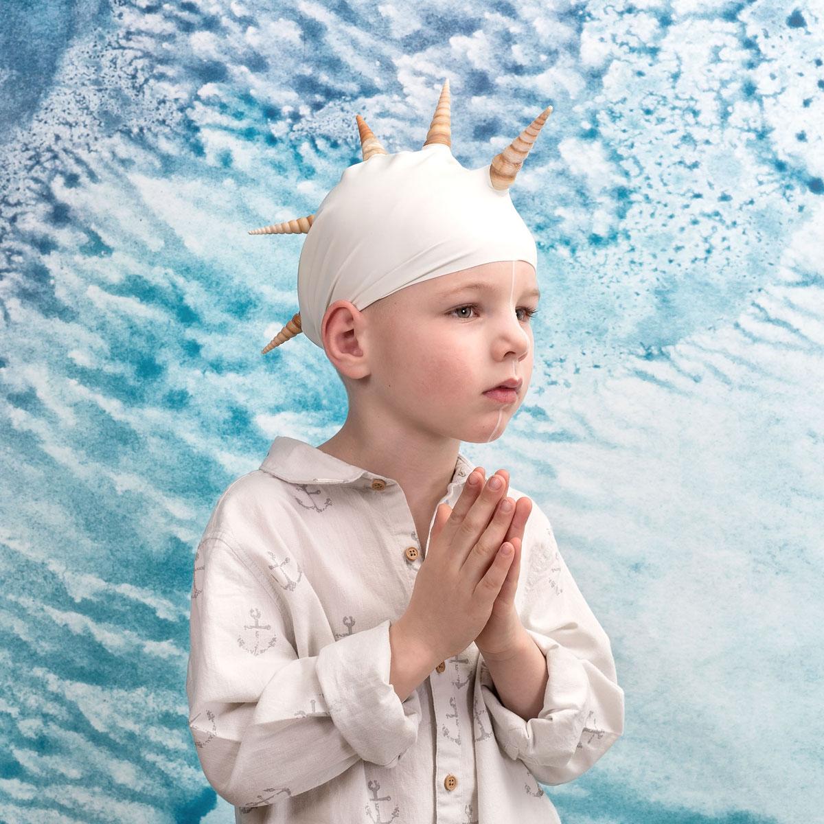 foto van jongetje metr badmuts op met hanenkammen van schelpen zijn handen voor zijn borst gevouwen als namaste met achtergrond van een witte schuimende zee