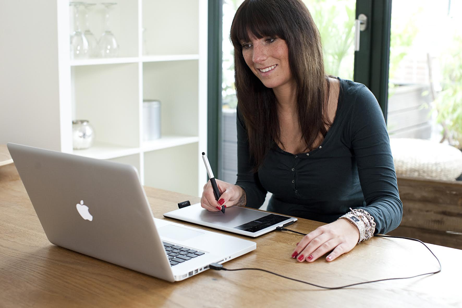 foto van vrouw die aan laptop werkt aan bureau en wacom tablet erbij gebruikt