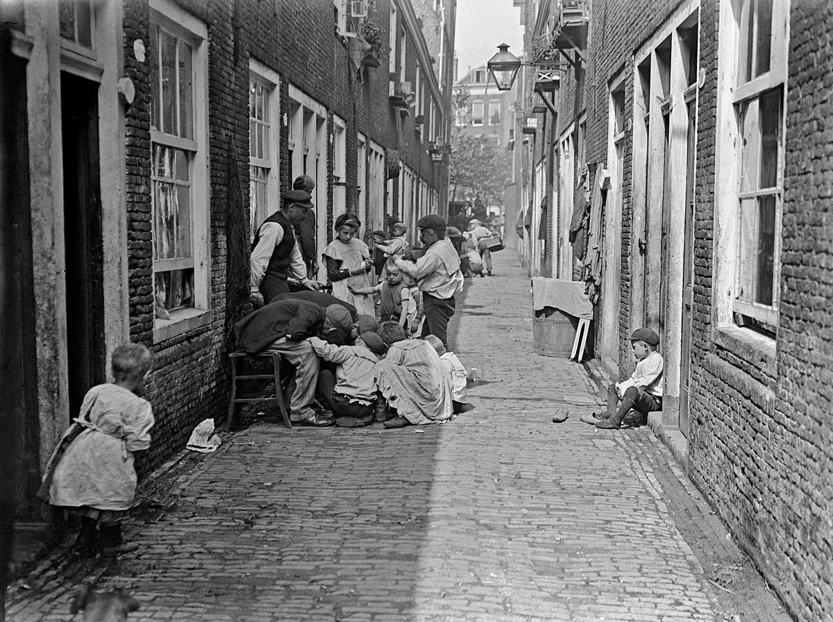 foto uit 1910 in zwartwit van een straatje in Rotterdam met mensen voor hun huis op stoel en staand en op grond