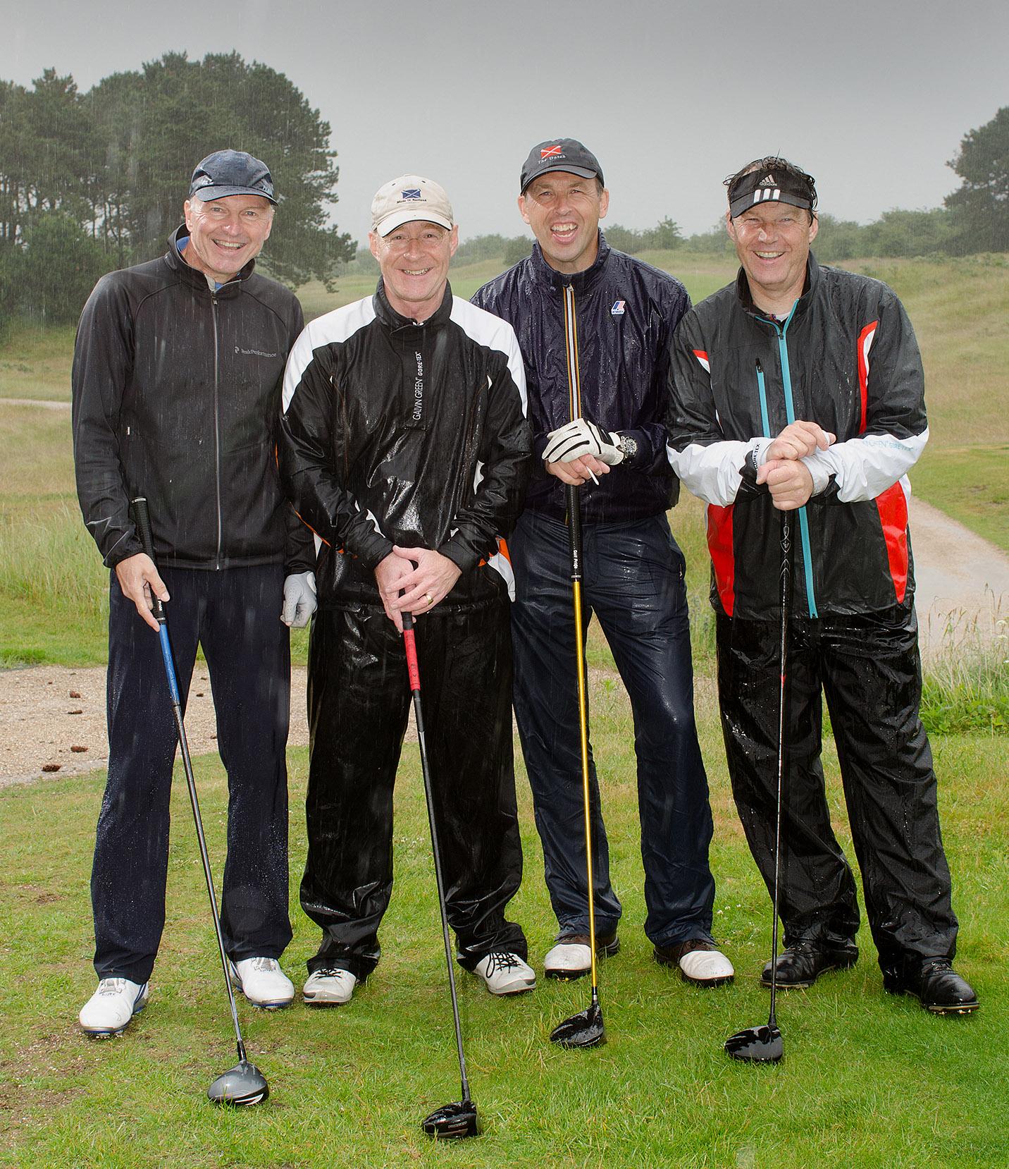 foto van vier mannen op de golfbaan in de regen lachend