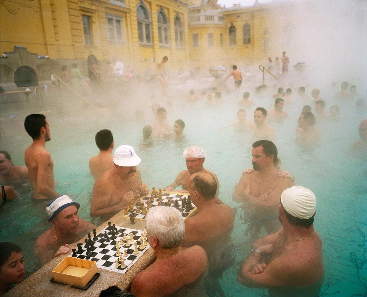 foto van mannen in een rivier met schaakborden en een geel gebouw op de achtergrond