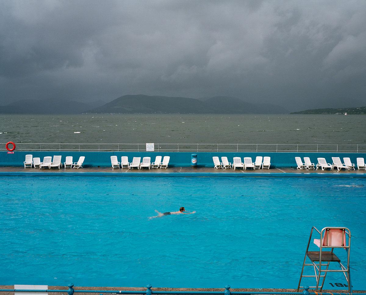 foto van een zwembad met een man die zwemt en langs de kant ligstoelen met uitzicht op de zee met bergen