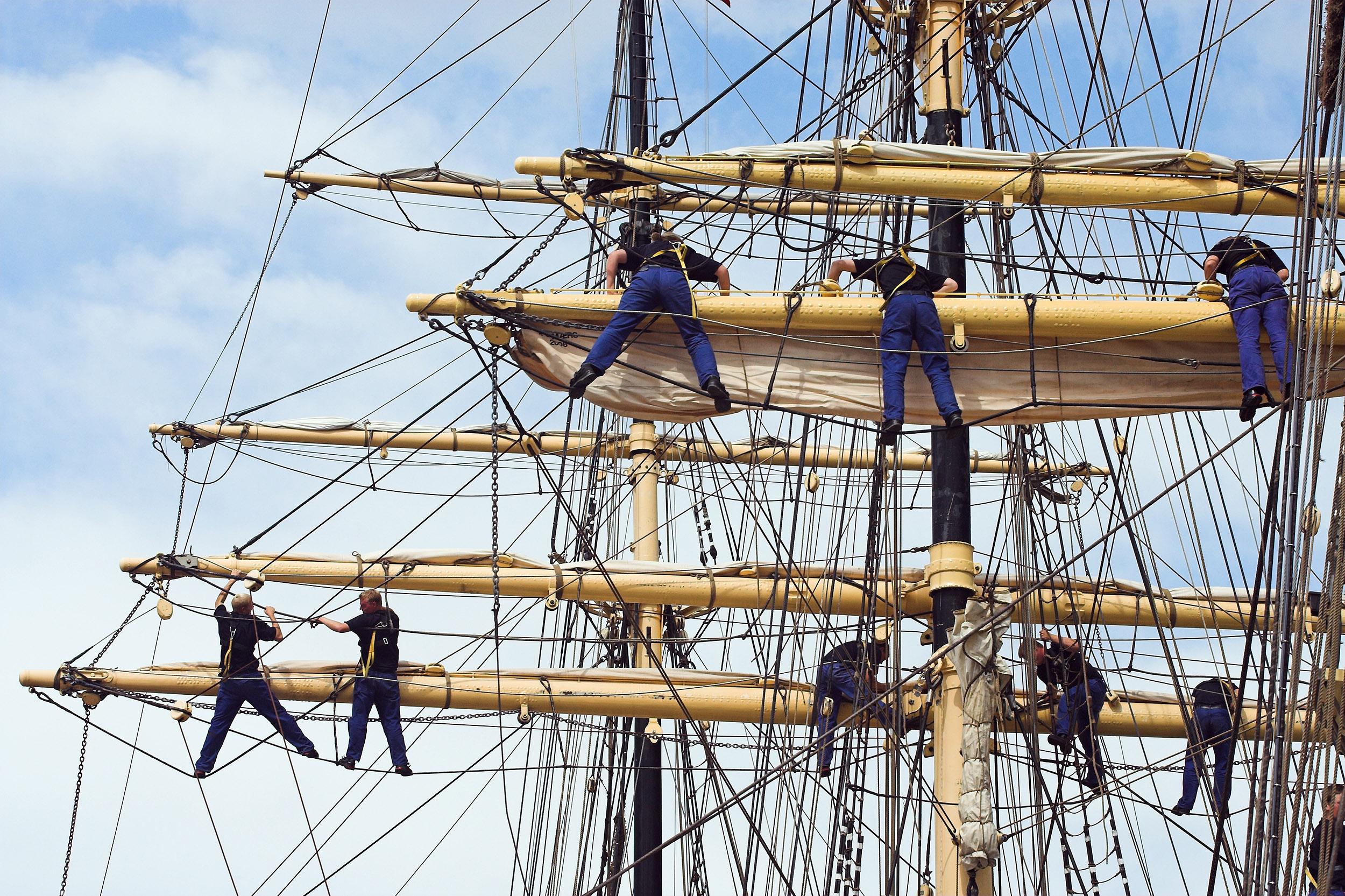 foto van matrozen die in groot zeilschip aan touwen hangen