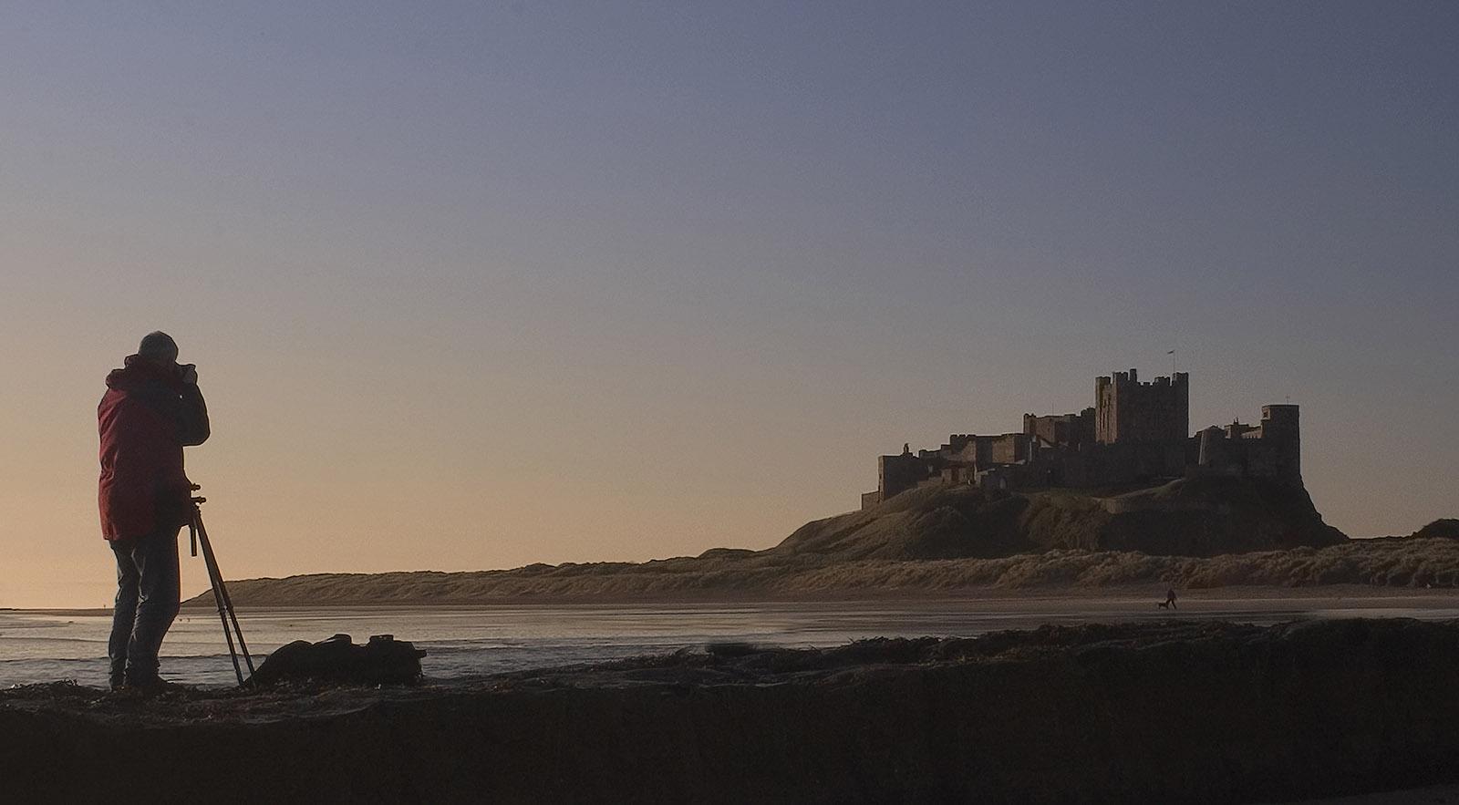 foto van man die foto maakt van oud kasteel op een berg bij de zee in avondlicht