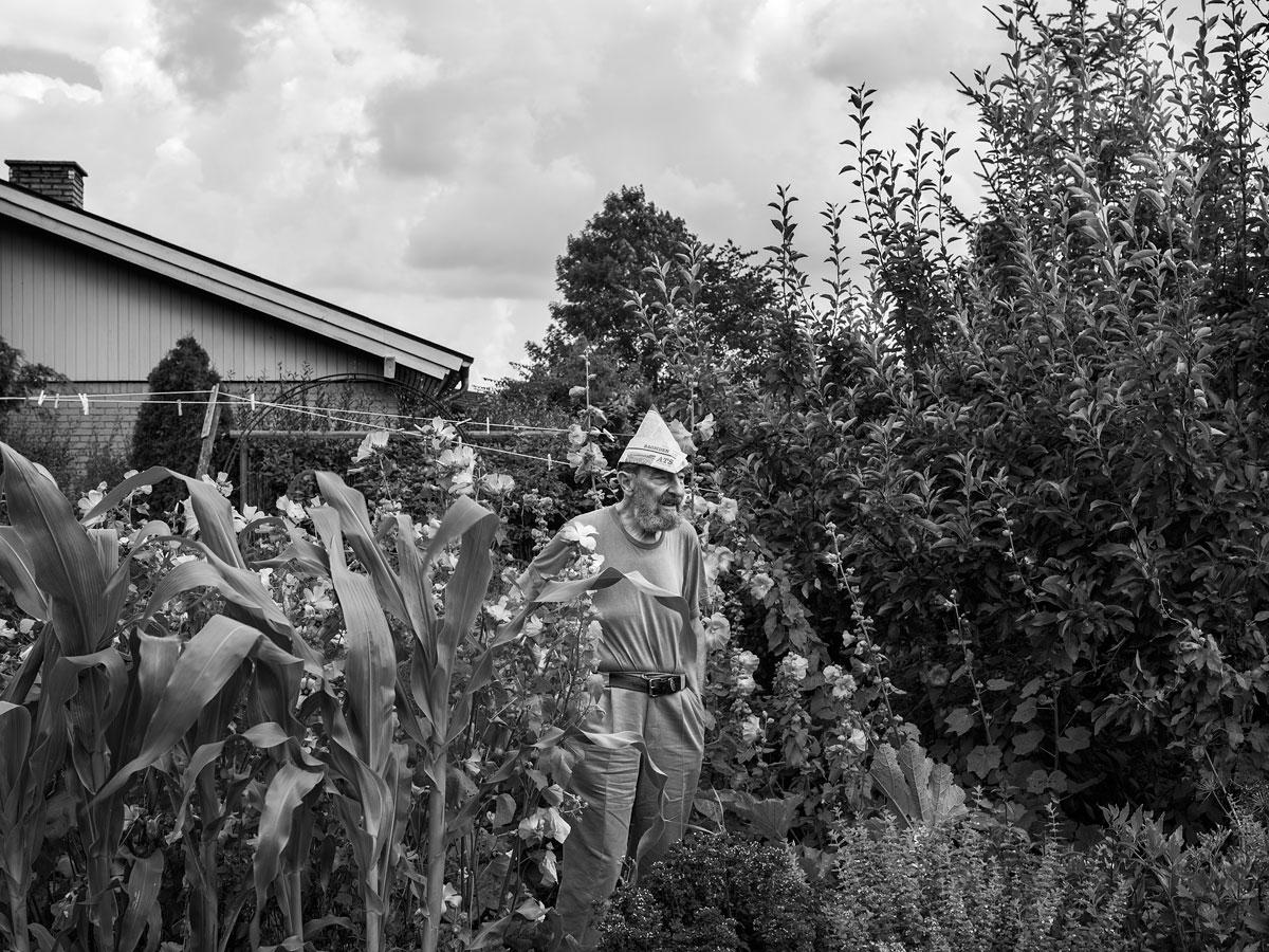 foto van een man met een papieren hoedje in tuin tussen hoge bloemen en struiken