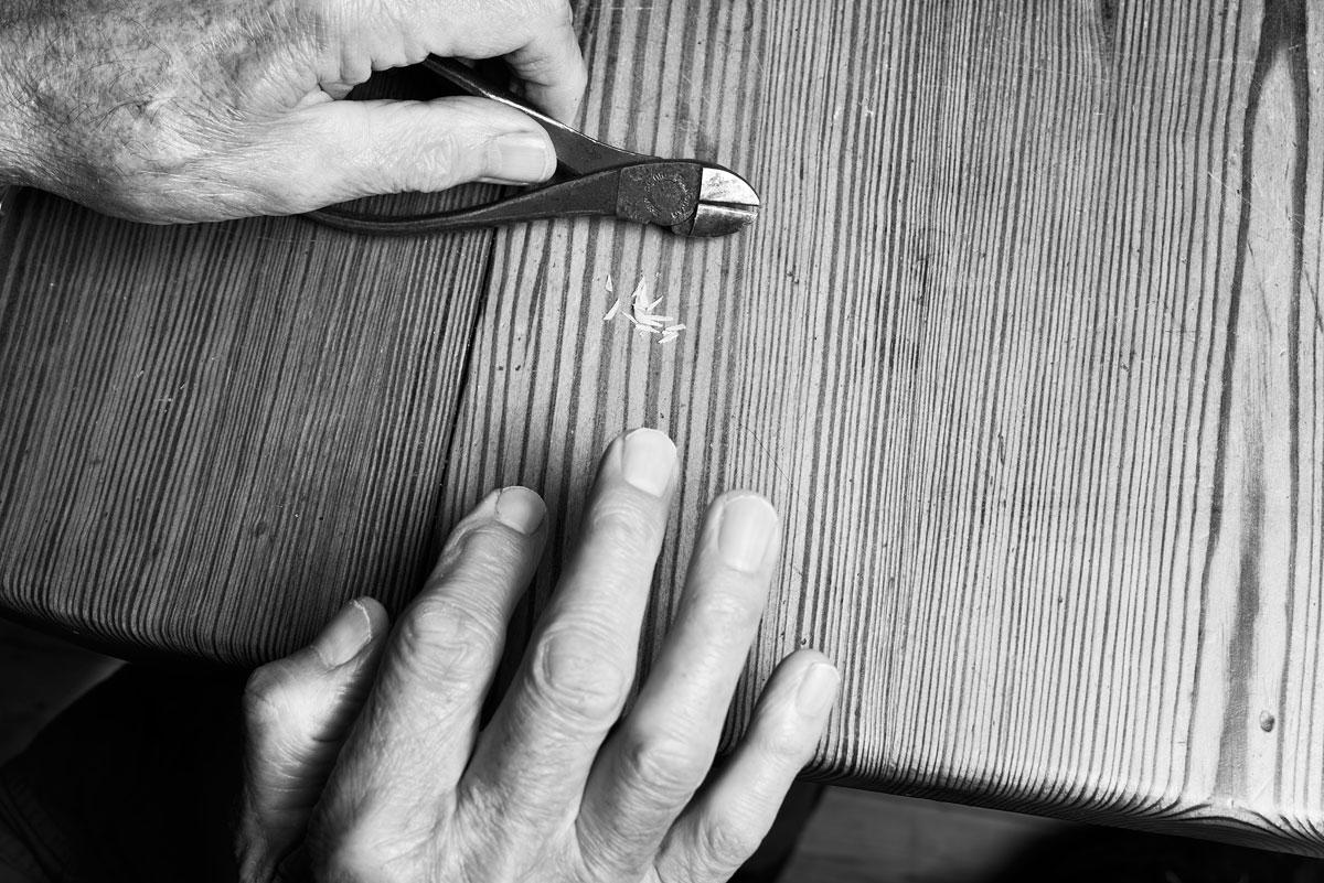foto van handen met een tang op een stuk hout