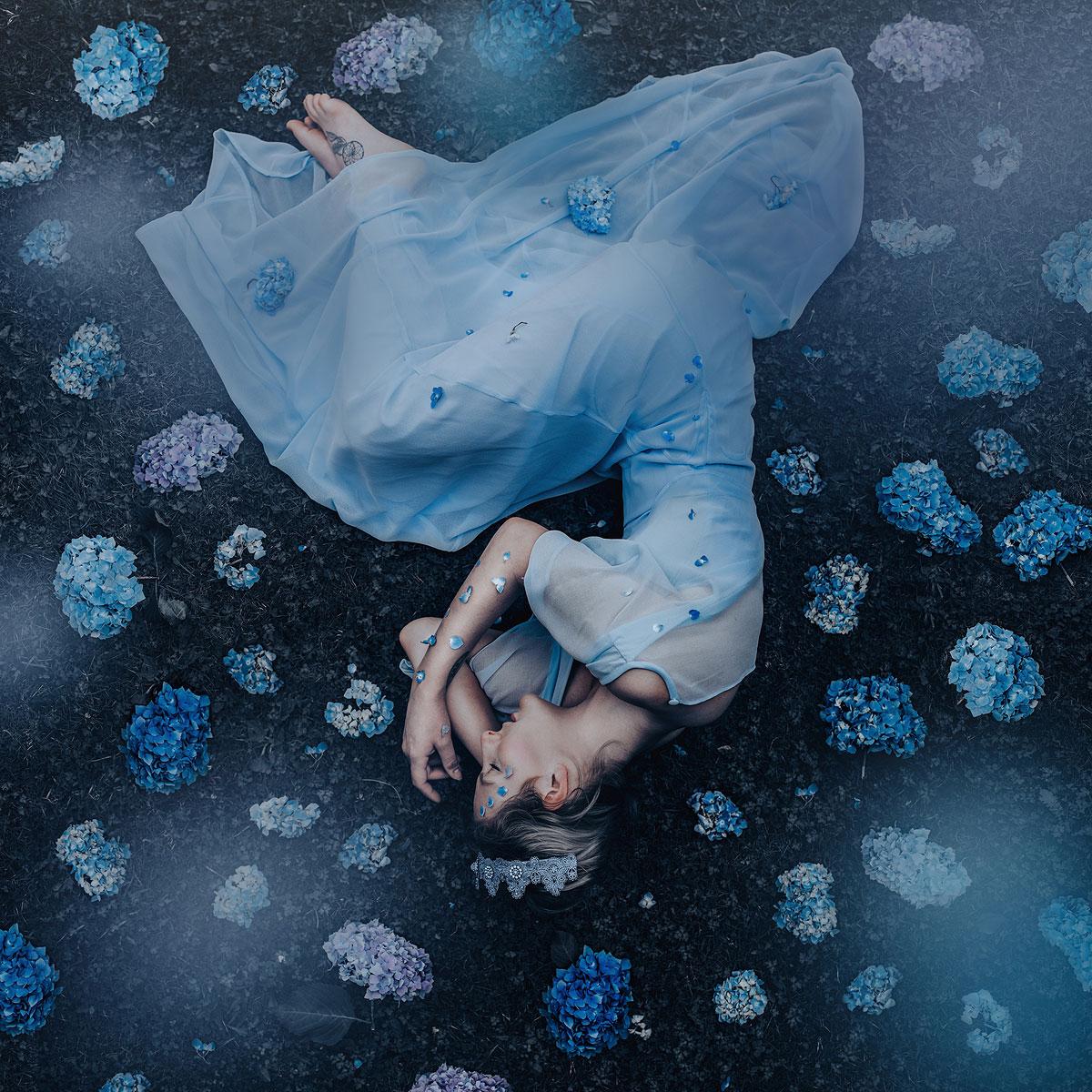 foto van een vrouw die op haar zij ligt, het hoofd onderaan, in een blauwe jurk met blauwe hortensia bloemen eromheen