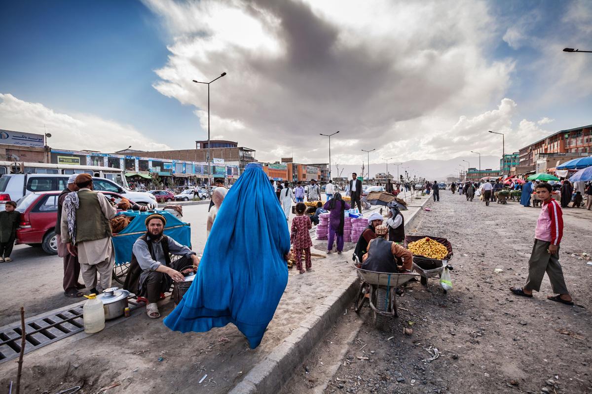 foto: Jeroen Swolfs. Afghanistan, Kabul, juni 2012. Een vrouw in burka haast zich door een straat in centrum Kabul waar allerhande producten op de stoep worden verkocht. Baghdad, Irak, december 2015. De duizend jaar oude boekenstraat Al-Mutanabbi werd in 2007 verwoest door een autobom. De straat werd herbouwd en de boekenmarkt trekt weer vele bezoekers.