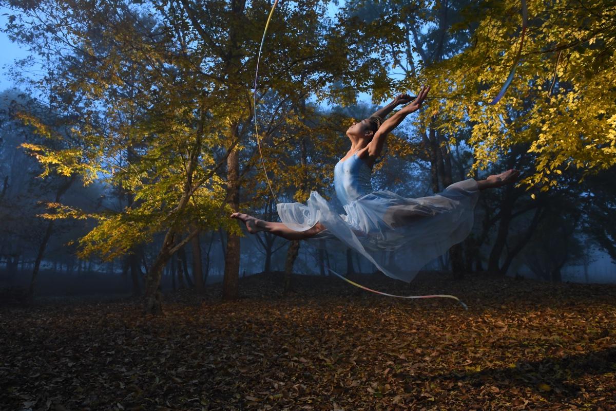 foto van een meisje in blauwe jurk die in een spagaat door de lucht zweeft in een herfstbos