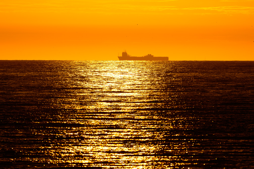 foto van zonweerspiegeling op zee met boot aan horizon en gele lucht