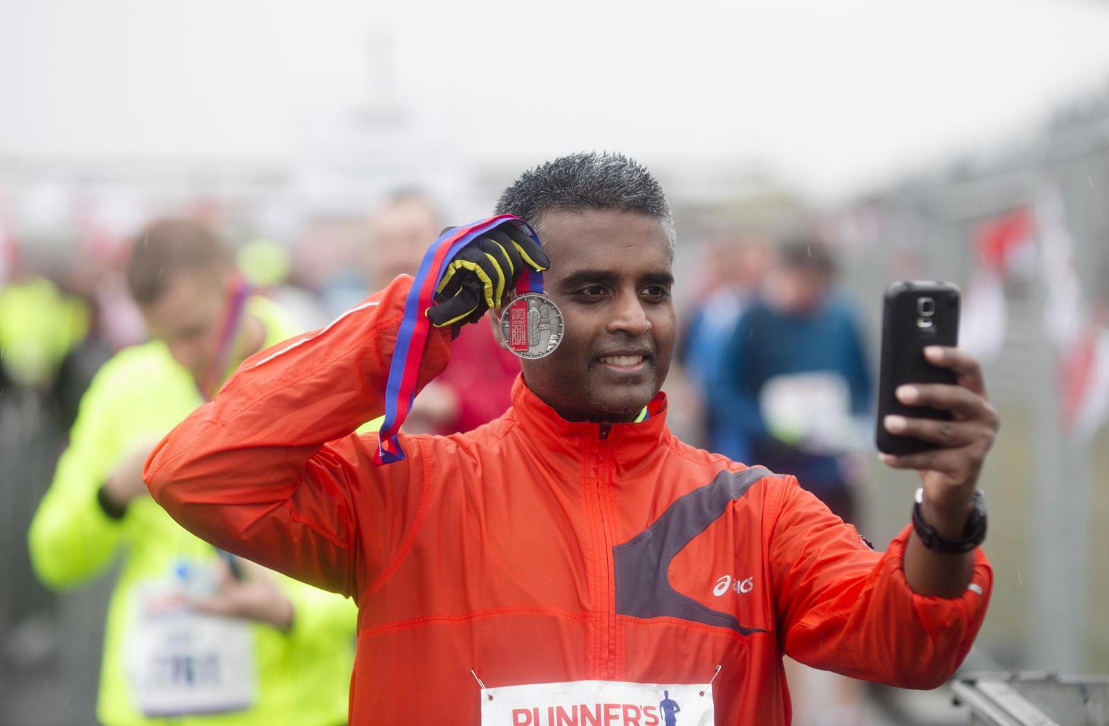 foto: © Bastiaan Heus - Zandvoort Circuit Run, man maakt selfie bij finish met medaille