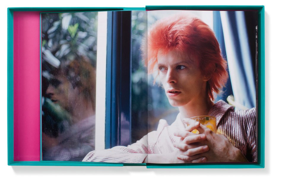 foto uit boek The Rise of David Bowie van jonge Bowie die met glas in hand bij raam zit