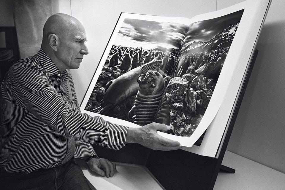 foto van Sebastião Salgado zittend bij grote uitgave van zijn boek Genesis