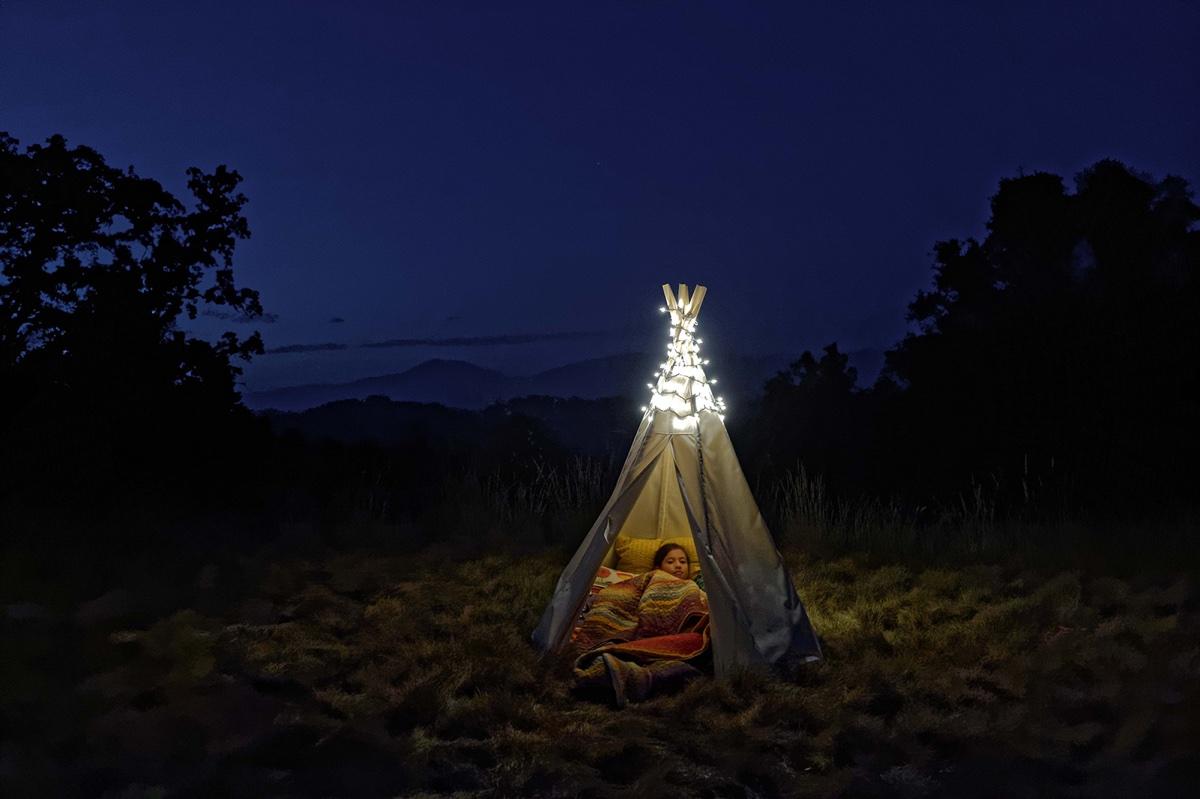 foto van tentje op een heide bij nacht met een kind erin