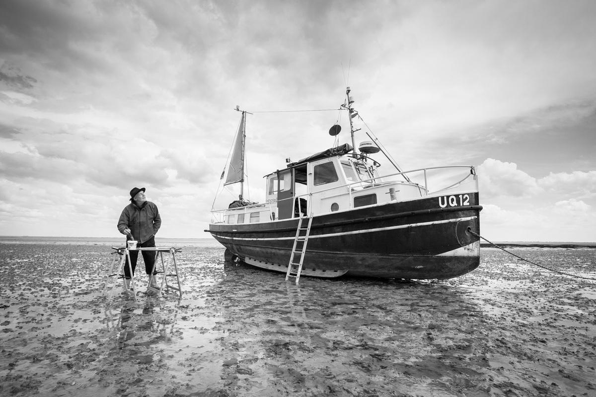 foto van waddenschilder op wadden met emmer verf en boot