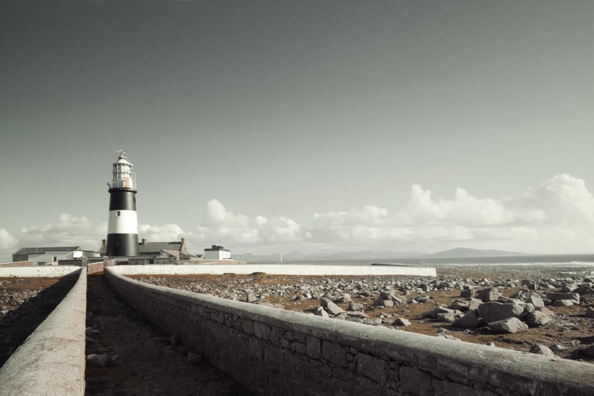 foto van kust vanuit muur met vuurtoren bekeken
