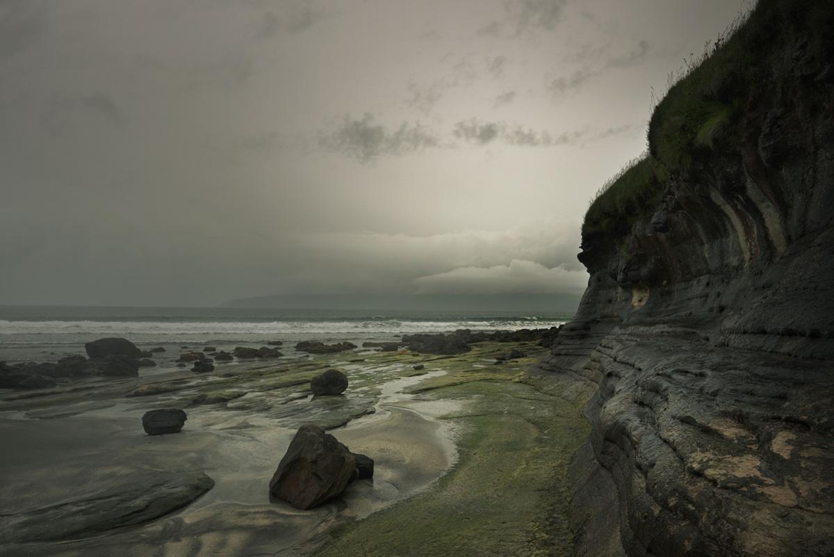 foto van kust met rotsen en grijze wolken