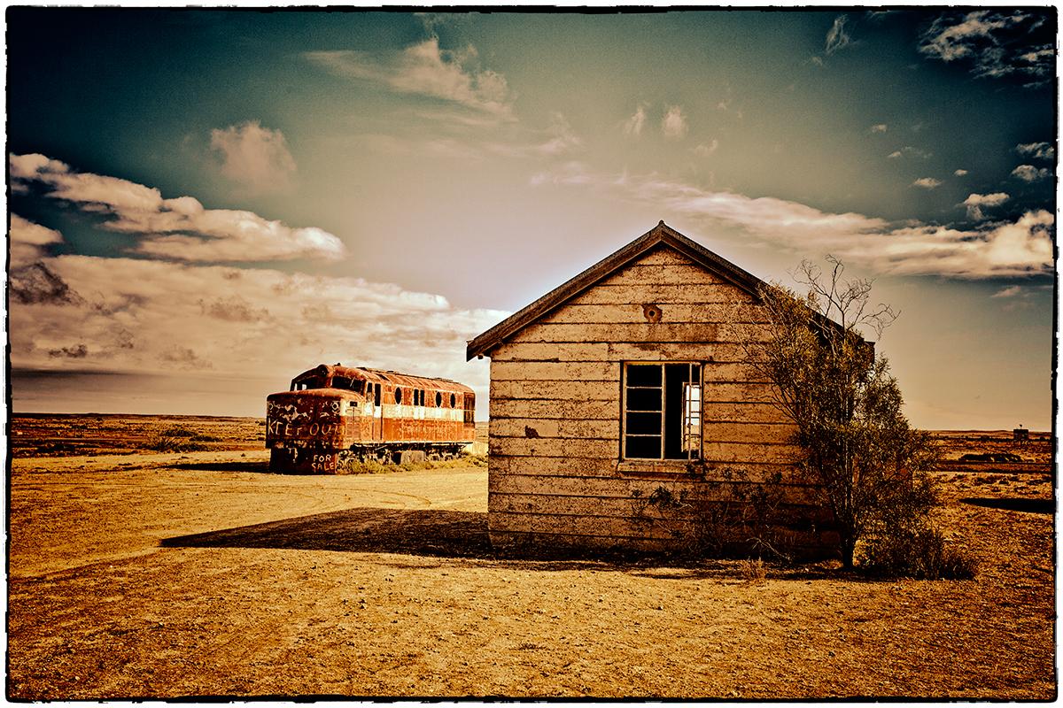 foto van een houten schuurtje en een oude stoomtrein in Australië in leeg landschap