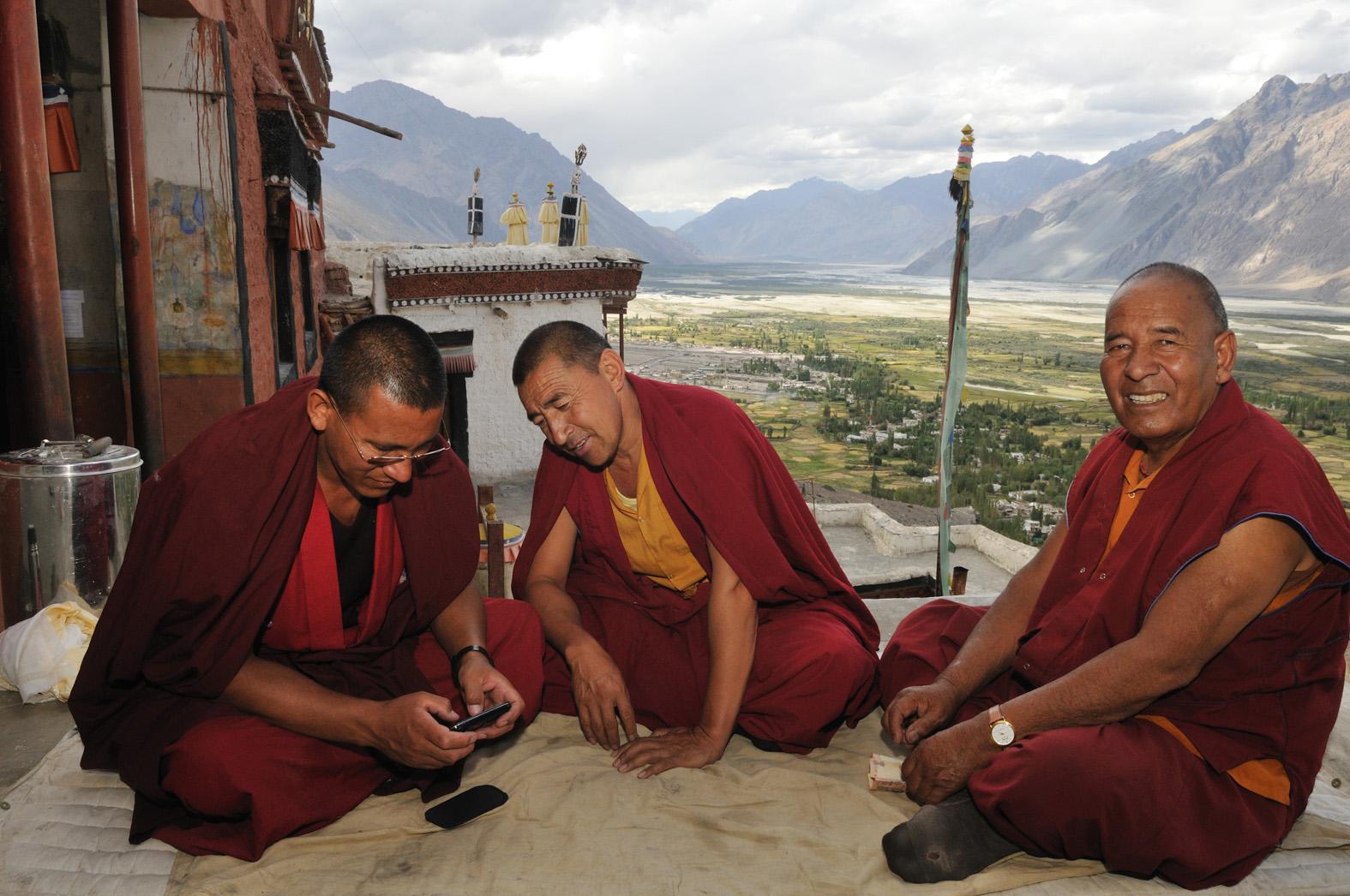 foto van monniken met mobieltje bij tempel en bergen