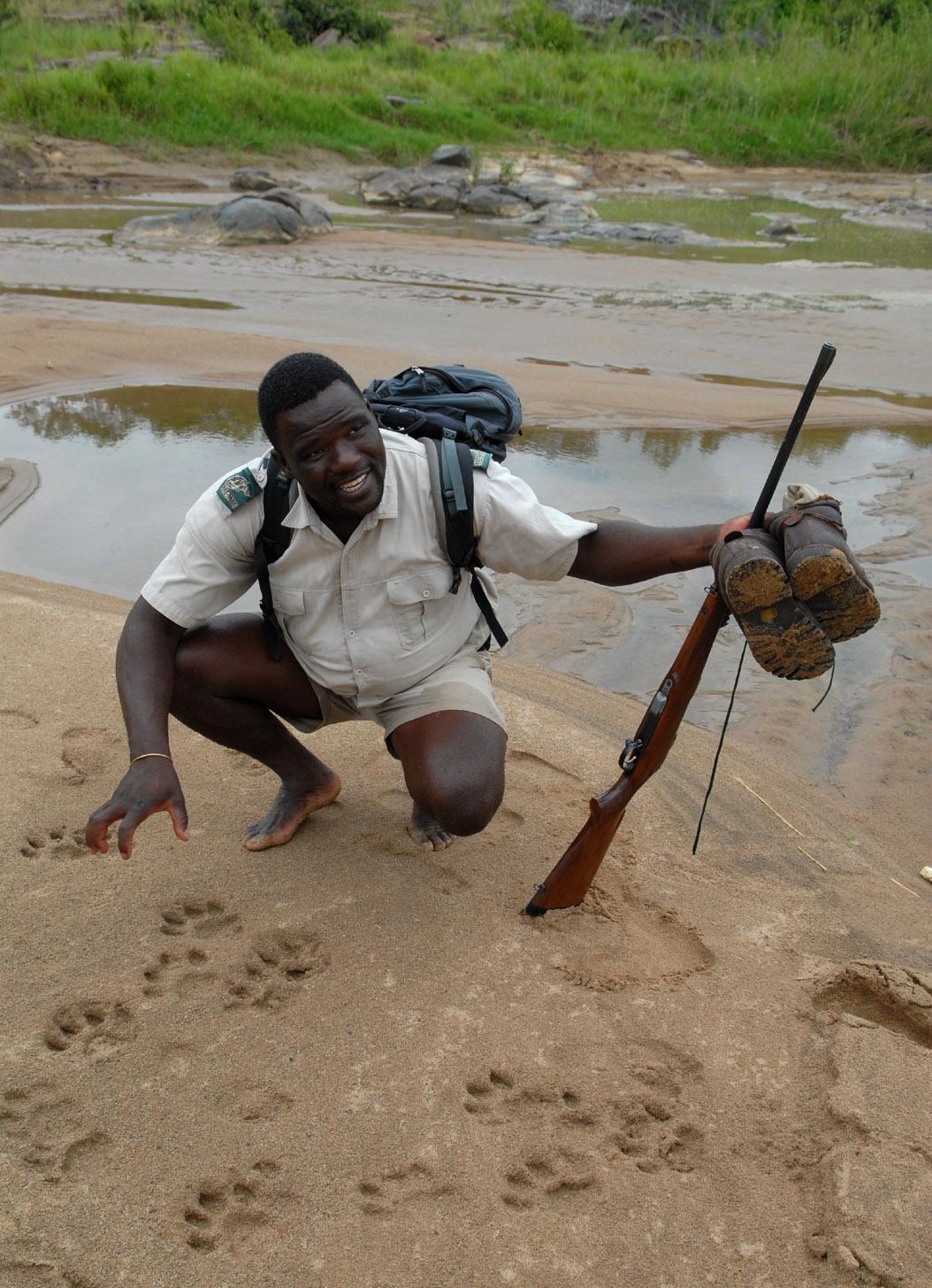 foto: Tom van der Leij van landschap Zuid-Afrika met reisgids geknield en met geweer in handen en schoenen uit in handen
