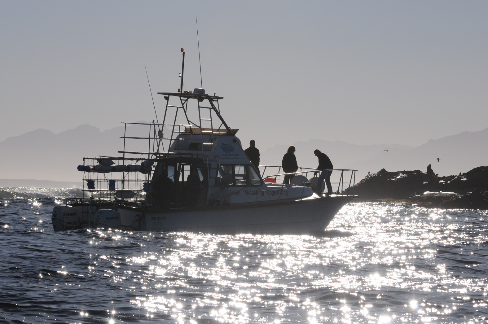 foto van schip voor cagediven op zee bij lage zon en weerspiegeling